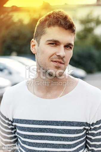 846124660istockphoto Handsome stylish man with a beard wearing a sweater at sunset. 645442980