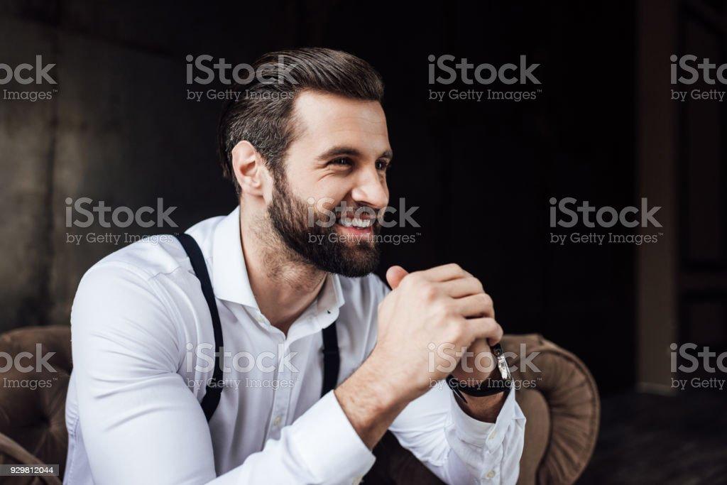 bel homme souriant élégant assis dans le fauteuil - Photo