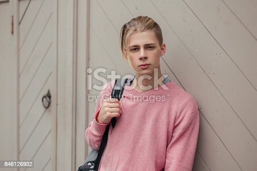 846124694 istock photo Handsome stylish young guy with a backpack near the wall 846126932