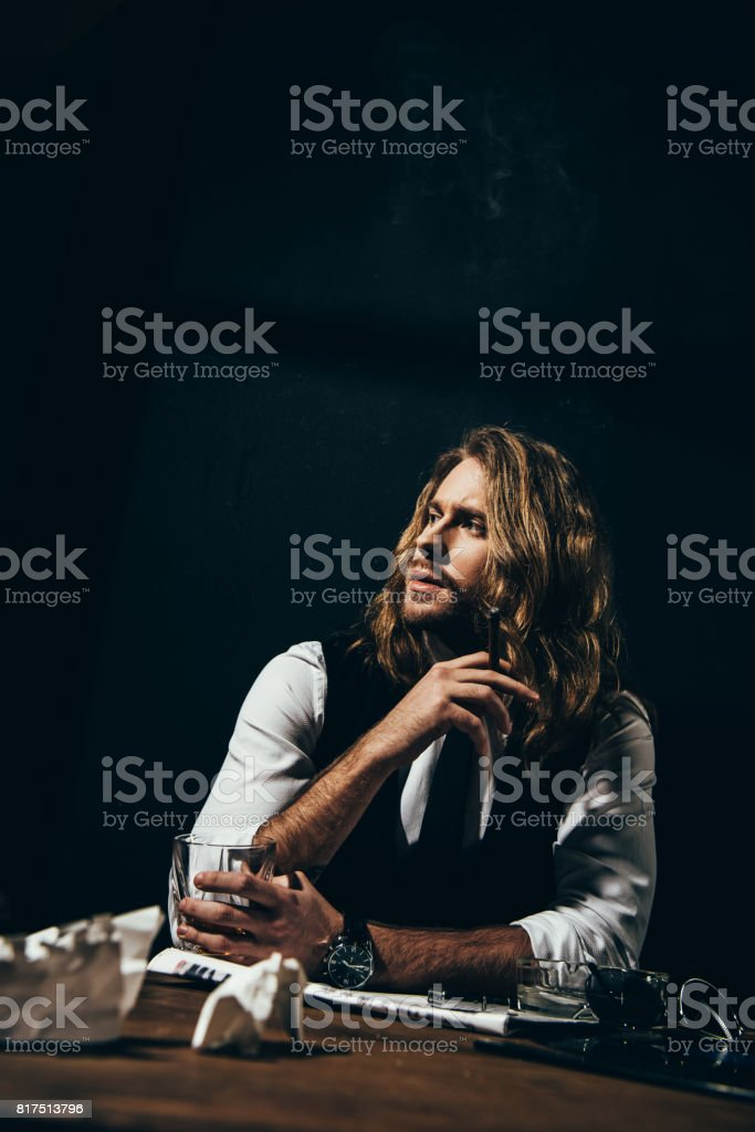 Handsome stylish young man drinking alcohol and smoking cigar while sitting at table stock photo