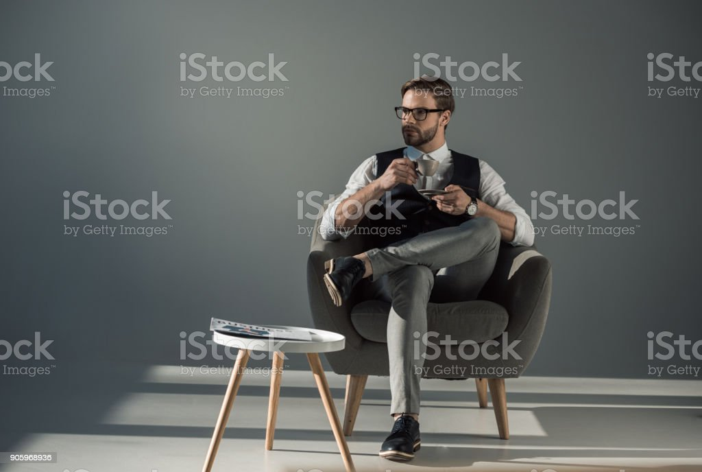 handsome stylish young man sitting in armchair and looking away while drinking coffee stock photo