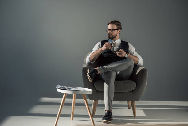 handsome stylish young man sitting in armchair and looking away while drinking coffee - preppy fashion stock photos and pictures