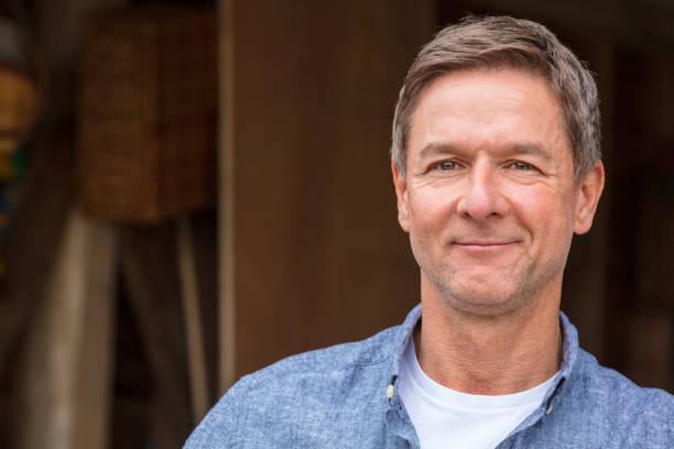 잘생긴, 성공적이 고 행복 한 중간 나이 든된 남자 남성 차고 또는 헛간에 의해 게시물에 기대 고 파란색 셔츠를 입고 - 성년 남자 뉴스 사진 이미지