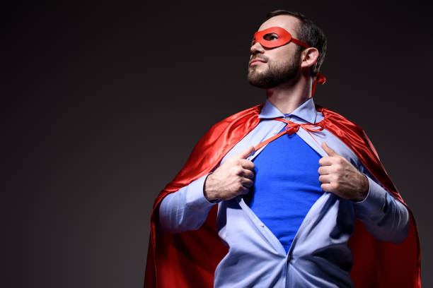 handsome super businessman in mask and cape showing blue shirt and looking away isolated on black - super hero stock pictures, royalty-free photos & images