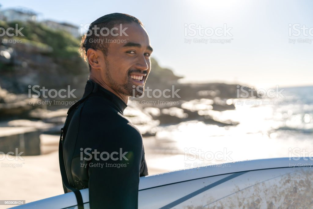 Handsome surfer carrying his board and looking at the camera smiling - Royalty-free Adult Stock Photo