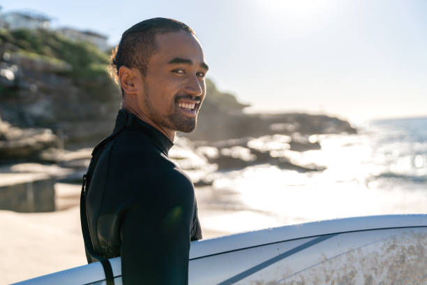 handsome surfer carrying his board and looking at the camera smiling - maori stock photos and pictures