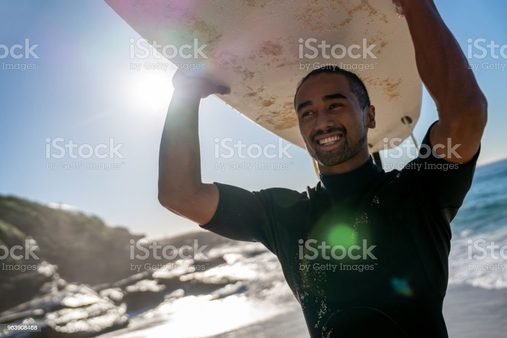 Handsome surfer carrying his board and looking very happy - Royalty-free Adult Stock Photo