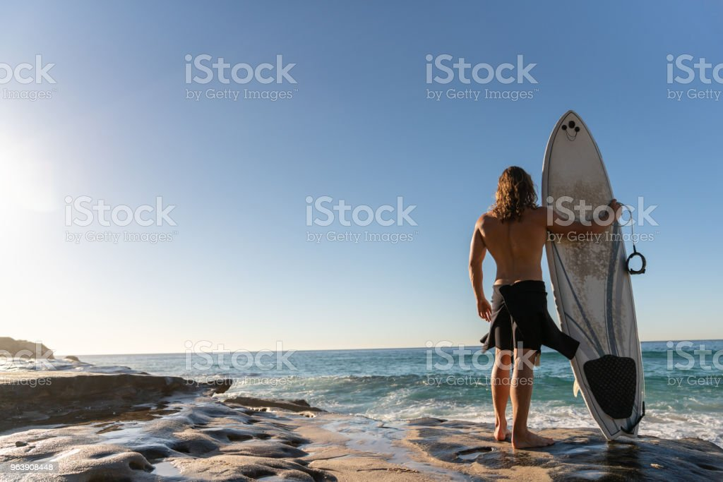 Handsome surfer carrying his board and watching the sunrise - Royalty-free Adult Stock Photo