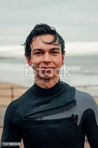 A headshot portrait of a young Caucasian man wearing a wetsuit, he has wet hair after going surfing in the sea. He is looking at the camera and smiling.
