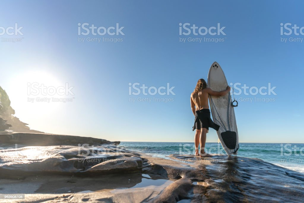 Handsome surfer looking at the ocean at the beach - Royalty-free Adult Stock Photo
