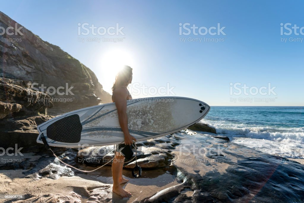 Handsome surfer looking at the sunrise at the beach - Royalty-free Adult Stock Photo