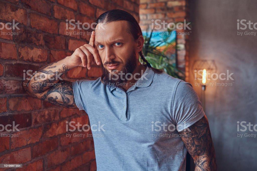 Ein Hubscher Tatowierten Mann Mit Eine Stilvolle Frisur Und Bart In