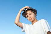 A portrait of a teenage boy, he is standing outside, wearing a white shirt against a blue sky. He is also wearing a hat, one hand is up at the hat, he is looking straight into the camera.