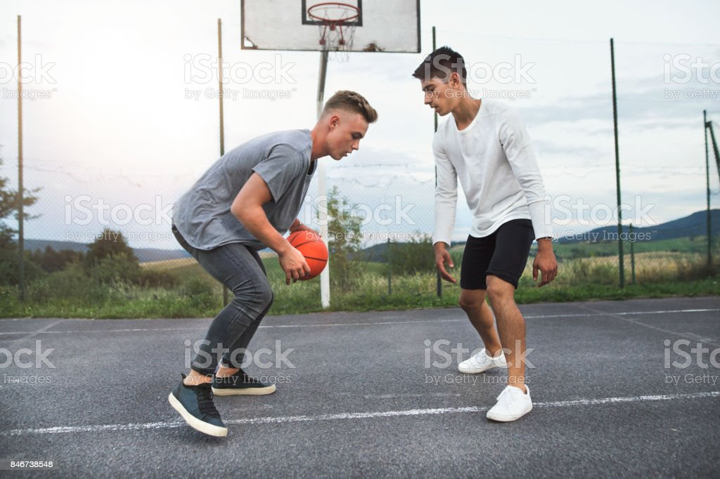 Handsome teenage boys playing basketball outdoors on playground. stock photo