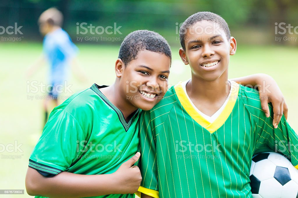 Handsome teenage soccer buddies smile proudly stock photo