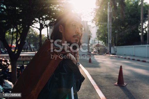 A young Thai man crossing the street and carrying a vintage bag over his shoulder.