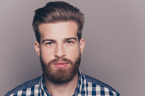 636829368 istock photo handsome thinking young man looking at camera on gray wall 636829368