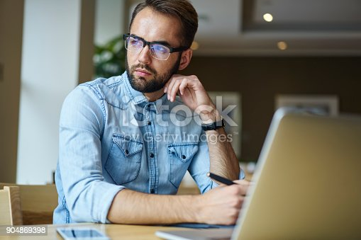 istock Handsome thoughtful bearded journalist in trendy eyeglasses looking away and thinking sitting at laptop computer in coffee shop.Pensive confident male entrepreneur in spectacles working remote 904869398