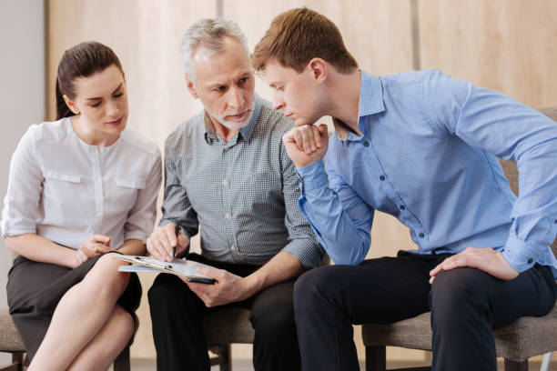 Handsome thoughtful man sitting with his colleagues stock photo