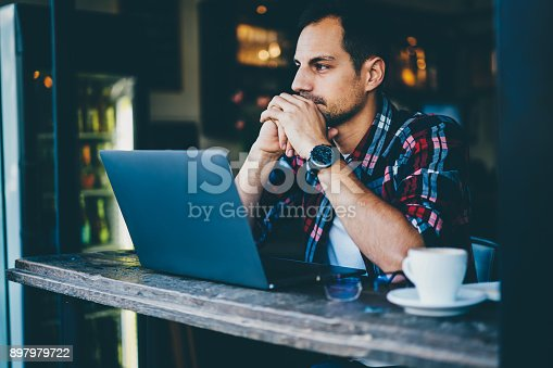 Handsome thoughtful young man designer sitting at digital netbook device and thinking on new ideas for creating modern graphic in stylish coffee shop interior with free high speed internet connection