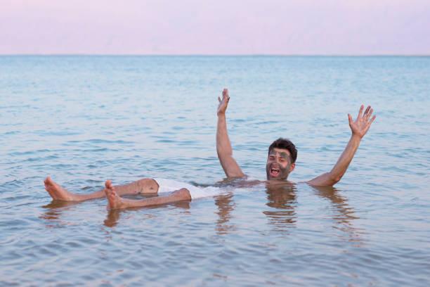 handsome tourist man floating in dead sea. - morze martwe zdjęcia i obrazy z banku zdjęć