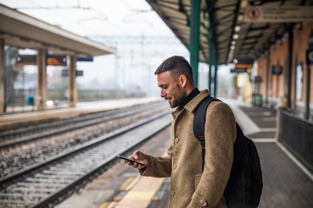 Schöne Tourist beobachten Inhalte auf seinem Handy warten auf Zug zu kommen - Stock Photo – Foto