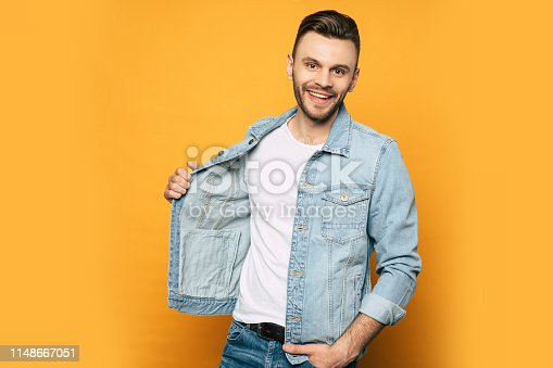 906807208istockphoto Handsome trendy and stylish beard man in denim shirt is posing over yellow background 1148667051