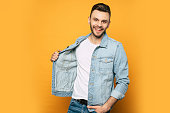 istock Handsome trendy and stylish beard man in denim shirt is posing over yellow background 1148667051