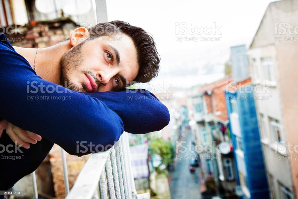Handsome turkish man day dreaming on his Istanbul balcony, looking...