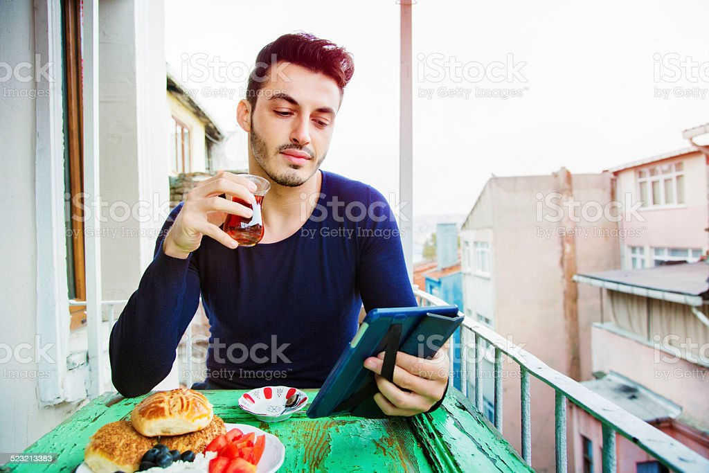 Handsome Turkish man enjoying media on his tablet during breakfast stock photo