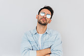 Handsome unshaved male model wearing trendy round mirror sunglasses and blue casual shirt posing against white background enjoying good summer weather. People, lifestyle and emotions concept.