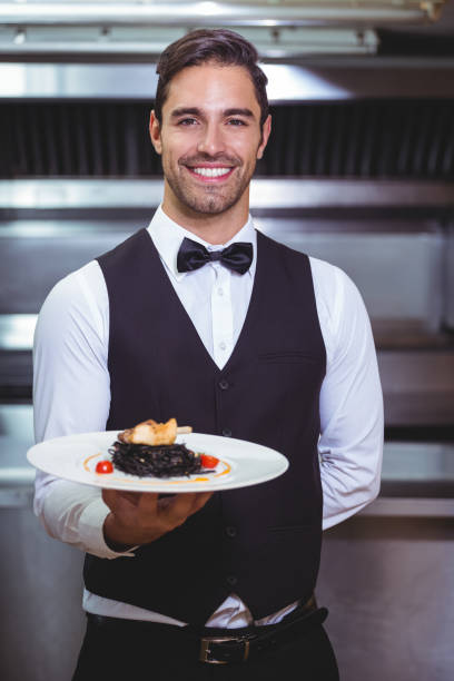 Handsome waiter holding a plate of squid ink spaghetti Handsome waiter holding a plate of squid ink spaghetti in the restaurant kitchen waiter stock pictures, royalty-free photos & images