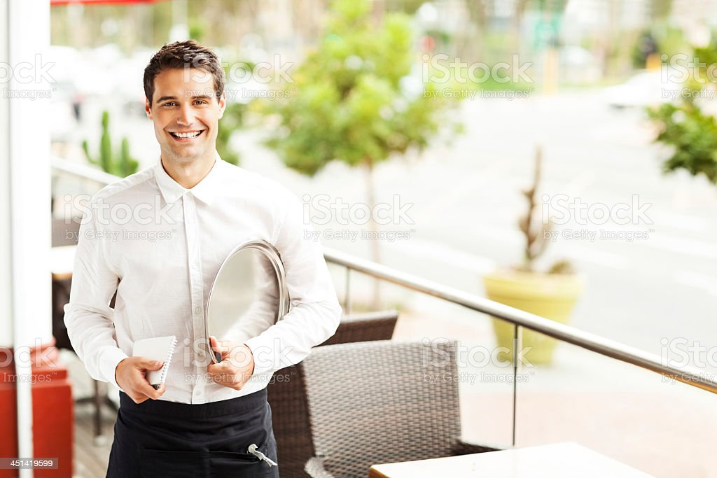 Handsome Waiter With Order Pad And Serving Tray In Restaurant royalty-free stock photo