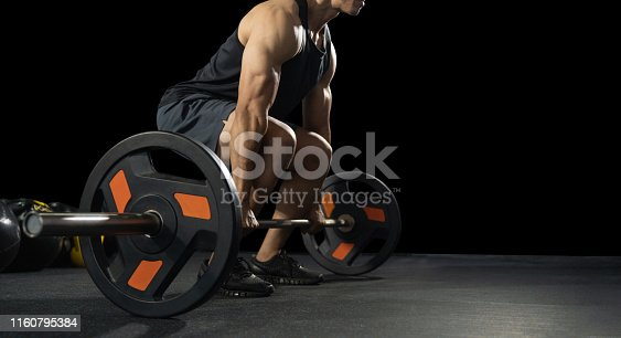 istock Handsome weightlifter preparing for training. Training with barbell, Athletic shirtless young sports man. Fitness model with barbell in gym 1160795384