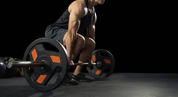 guapo levantador de pesas preparándose para el entrenamiento. entrenamiento con barbell, joven deportista sin camisa atlético. modelo de fitness con barbell en gimnasio - culturismo fotografías e imágenes de stock