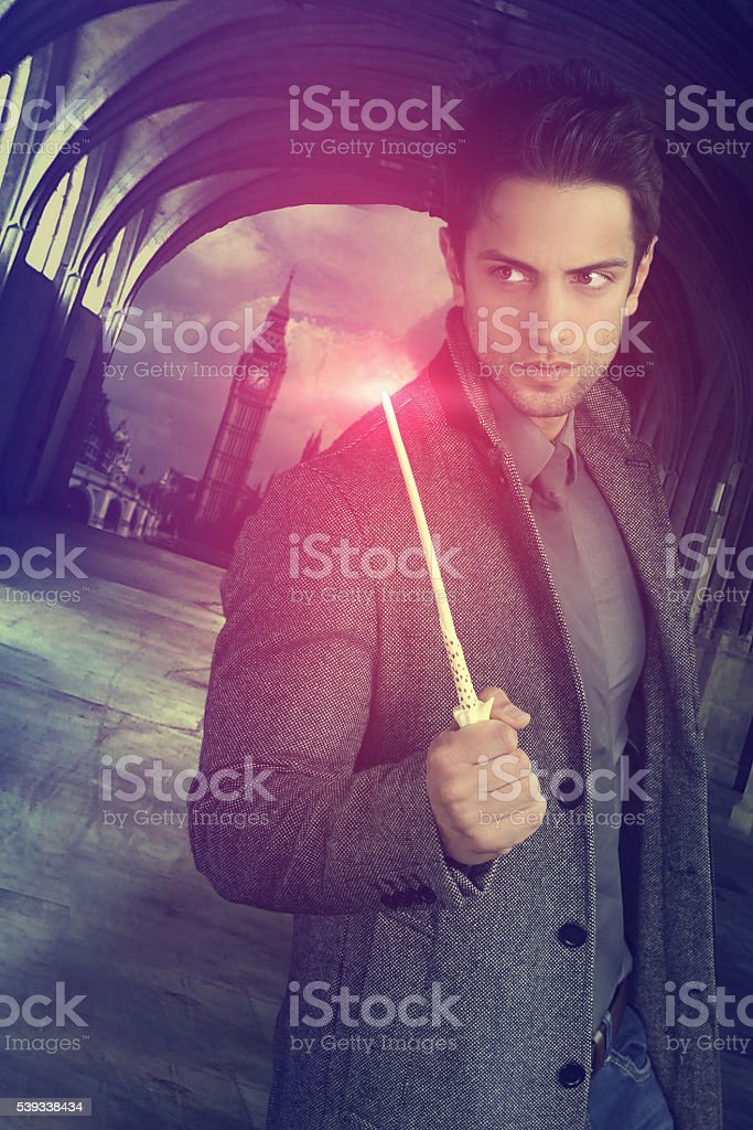 handsome wizard holding a magic wand stock photo