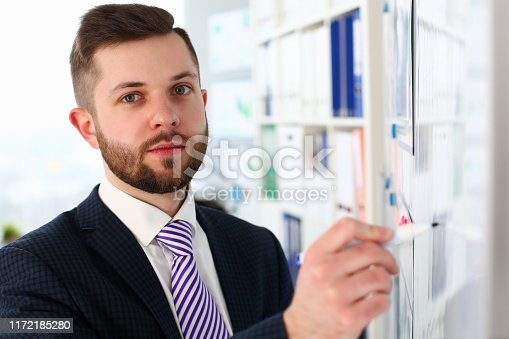 Portrait of smart male wearing classy suit and looking at camera with concentration. Attractive corporate manager firmly holding writing pen and posing in modern office. Company meeting concept