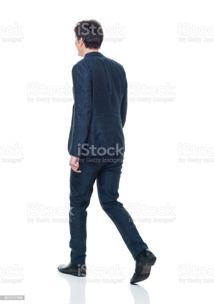 Handsome young adult male in business attire walking stock photo