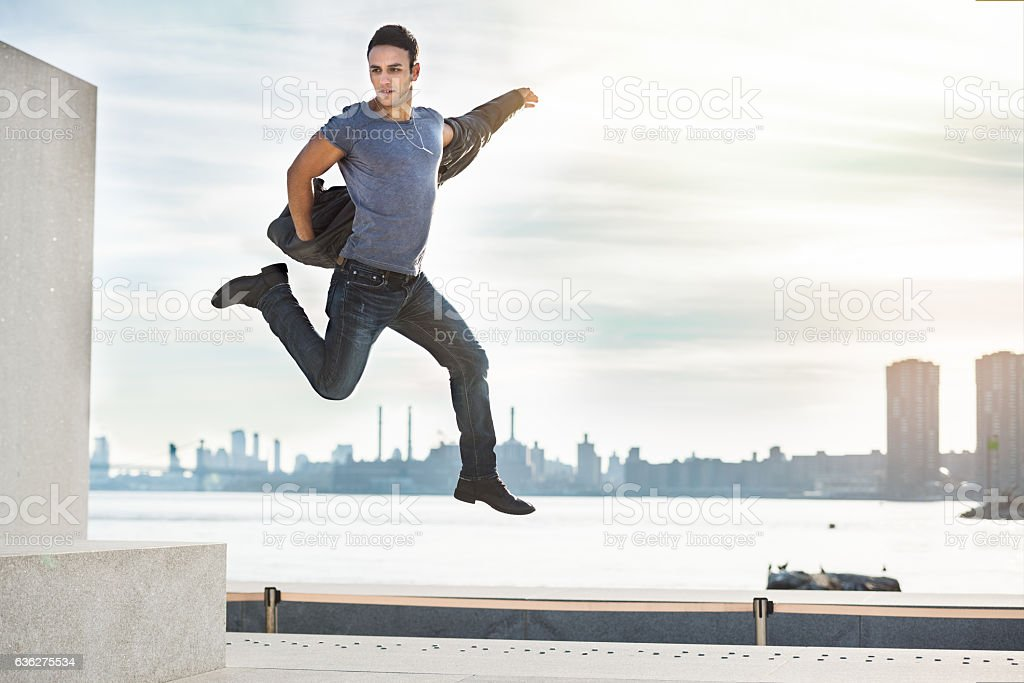 Handsome young adult man having fun and jumping in city stock photo