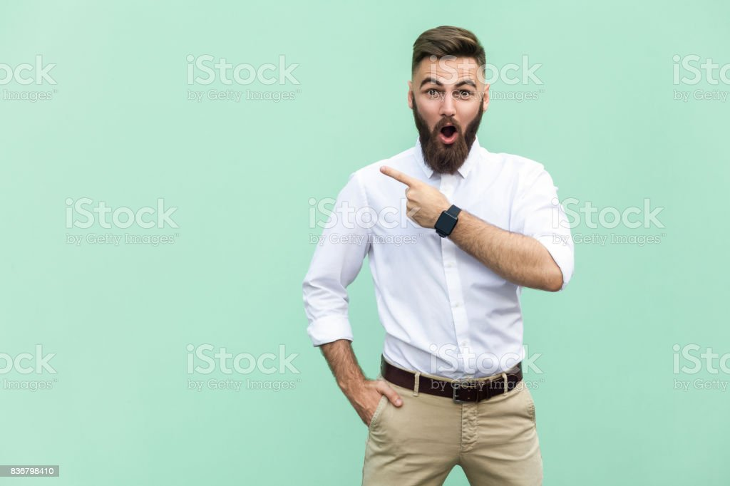 Handsome young adult man with beard in shoked. Pointing away while standing isolated on light green background royalty-free stock photo