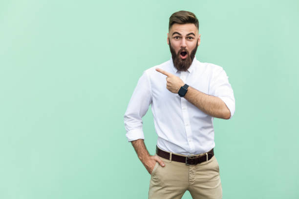 handsome young adult man with beard in shoked. pointing away while standing isolated on light green background - finger point stock photos and pictures