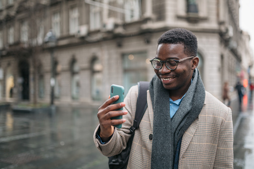 Happy young African American male freelancer walking around the city on a rainy day, smiling and using a smart phone