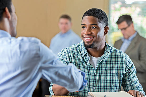 handsome young african american man at job interview - job search stock photos and pictures