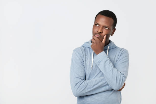knappe jonge afro-amerikaanse man te kijken met doordachte en sceptische expressie - achterdocht stockfoto's en -beelden