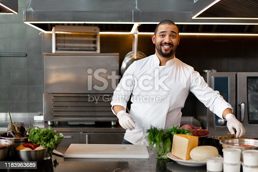 Handsome young African chef standing in professional kitchen in restaurant preparing a meal of meat and cheese vegetables. Portrait of man in cook uniform. Healthy eating concept.