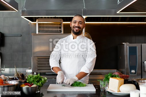 Handsome young African chef standing in professional kitchen in restaurant preparing a meal of meat and cheese vegetables. Portrait of man in cook uniform Cuts dill with a metal knife.