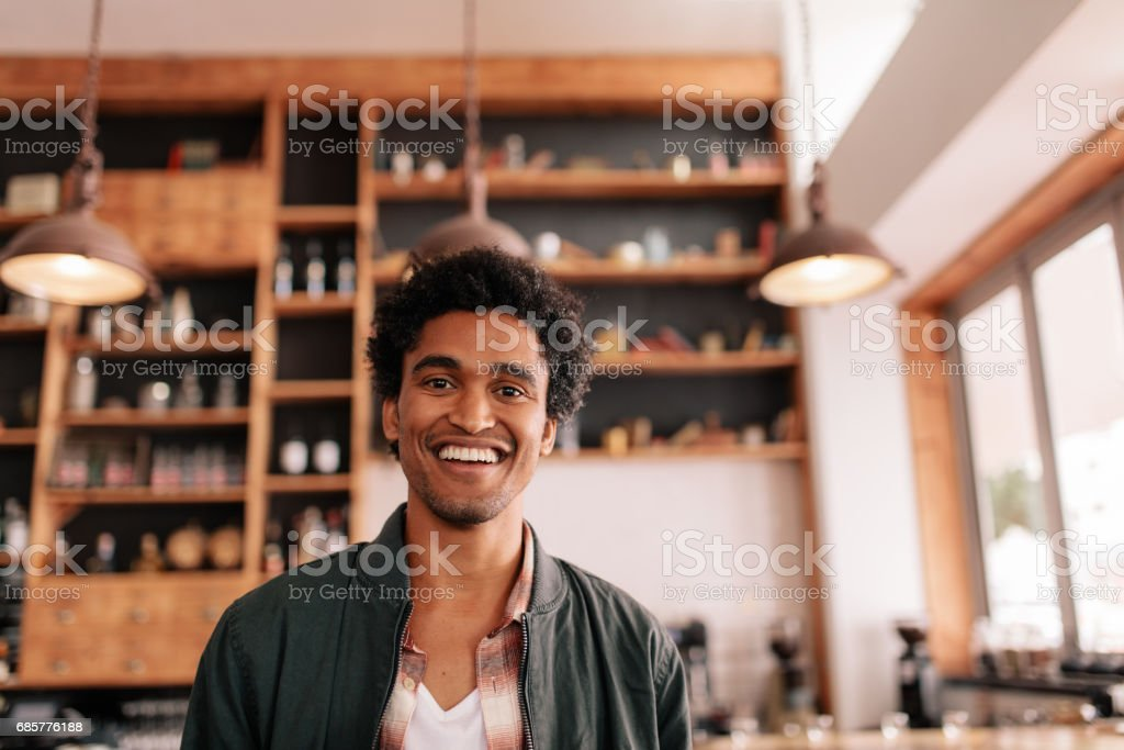 Handsome young african guy standing in a coffee shop and smiling 免版稅 stock photo