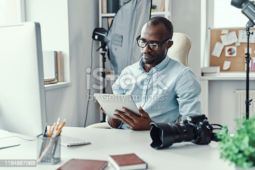Handsome young African man using digital tablet while working in the modern office