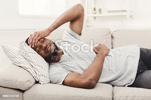 istock Handsome young african-american man suffering from stomachache and headache 896203258