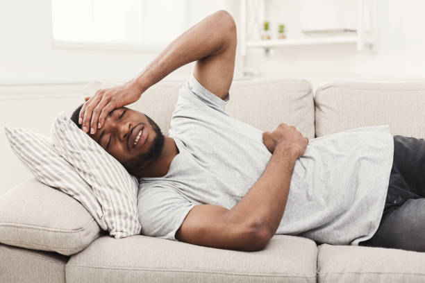 handsome young african-american man suffering from stomachache and headache - china drug foto e immagini stock